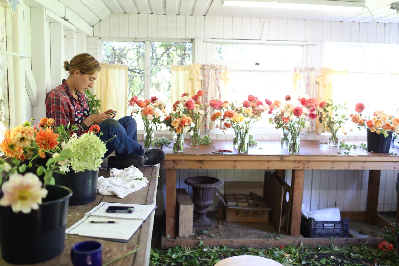 Erin Benzakein regarde son téléphone dans le studio Floret